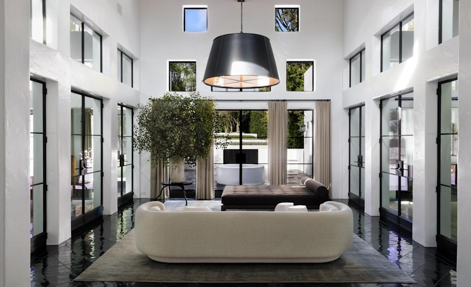 """""""The white stucco walls, dark oak beams, and black stone floors gave the house an almost monastic feel, a purity emphasized by Ryan's insistence that the walls remain unadorned by art,"""" Shadley writes about Ryan Murphy. This room in his Pacific Palisades home features a double-height ceiling with multiple square windows that drench it in light."""