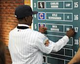 Shortstop Nick Gordon from Olympia high school in Windemere, Florida puts his name onto the board after being selected by the Minnesota Twins with the fifth pick in the 2014 MLB baseball draft Thursday, June 5, 2014, in Secaucus, N.J. (AP Photo/Bill Kostroun)