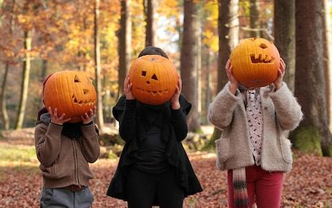 Two girls and a boy are playing in the woods, covering their faces with carved halloween pumpkins - Credit: Susan K/Getty Images