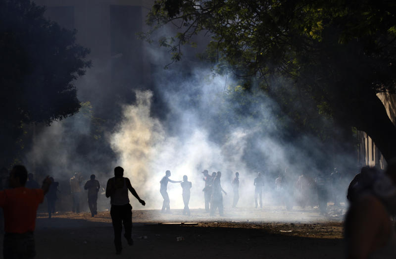Demonstrators are seen through the haze of tear gas during clashes with the Egyptian security close to the interior ministry in Cairo, Egypt, early Wednesday, June 29, 2011. Egyptian security forces and protesters are clashing for a second successive day in central Cairo in scenes not seen since the uprising that toppled Hosni Mubarak earlier this year.  (AP Photo/Khalil Hamra)