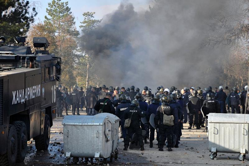 Bulgarian riot police stand near garbarge bins during clashes in the migrants reception centre in the town of Harmanli on November 24, 2016 (AFP Photo/)