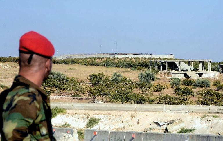 A member of the Syrian regime forces stares at a Turkish observation post in the town of Morek (AFP Photo/Maher AL MOUNES)