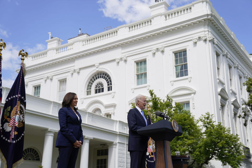 FILE - In this May 13, 2021, file photo Vice President Kamala Harris listens as President Joe Biden speaks on updated guidance on face mask mandates and COVID-19 response, in the Rose Garden of the White House in Washington. The Centers for Disease Control and Prevention said Thursday that fully vaccinated people — those who are two weeks past their last required dose of a COVID-19 vaccine — can stop wearing masks outdoors in crowds and in most indoor settings. Across Washington, the government is adjusting in a variety of ways to new federal guidance easing up on when face masks should be worn. (AP Photo/Evan Vucci, File)