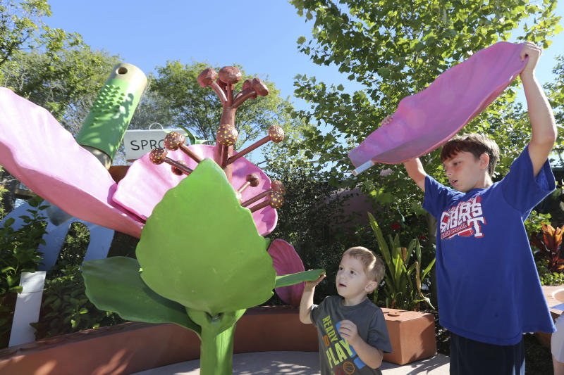 """In this Monday, Sept. 23, 2013 photo, Jacob Brown, 10, right, and Noah Workman, 3, assemble giant flower petals meant to teach parts of the plant at the Rory Meyers Children's Adventure Garden at the Dallas Arboretum, in Dallas. The arboretum that sprawls out on the edge of Dallas' White Rock Lake unveiled the $62 million new children's garden that aims to teach kids lessons in science while they have fun in the lush landscape. """"We can teach better about nature in nature,"""" says Mary Brinegar, president and chief executive officer of the Dallas Arboretum and Botanical Garden. (AP Photo/LM Otero)"""