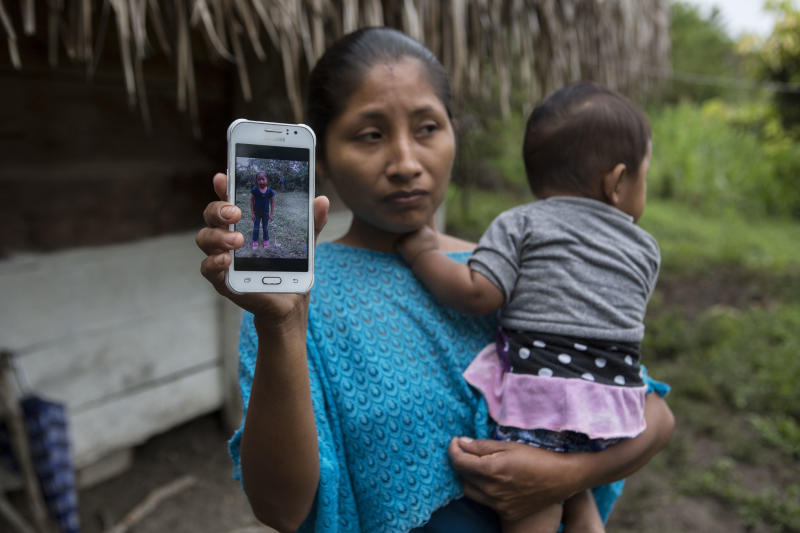 Claudia Maquin, 27, poses for a photo holding her brother-in-law's cell phone that shows an image of her daughter Jakelin Caal, in Raxruha, Guatemala, Saturday, Dec. 15, 2018. Jakelin, 7-years-old, died in a Texas hospital, two days after being taken into custody by border patrol agents in a remote stretch of New Mexico desert. (AP Photo/Oliver de Ros)