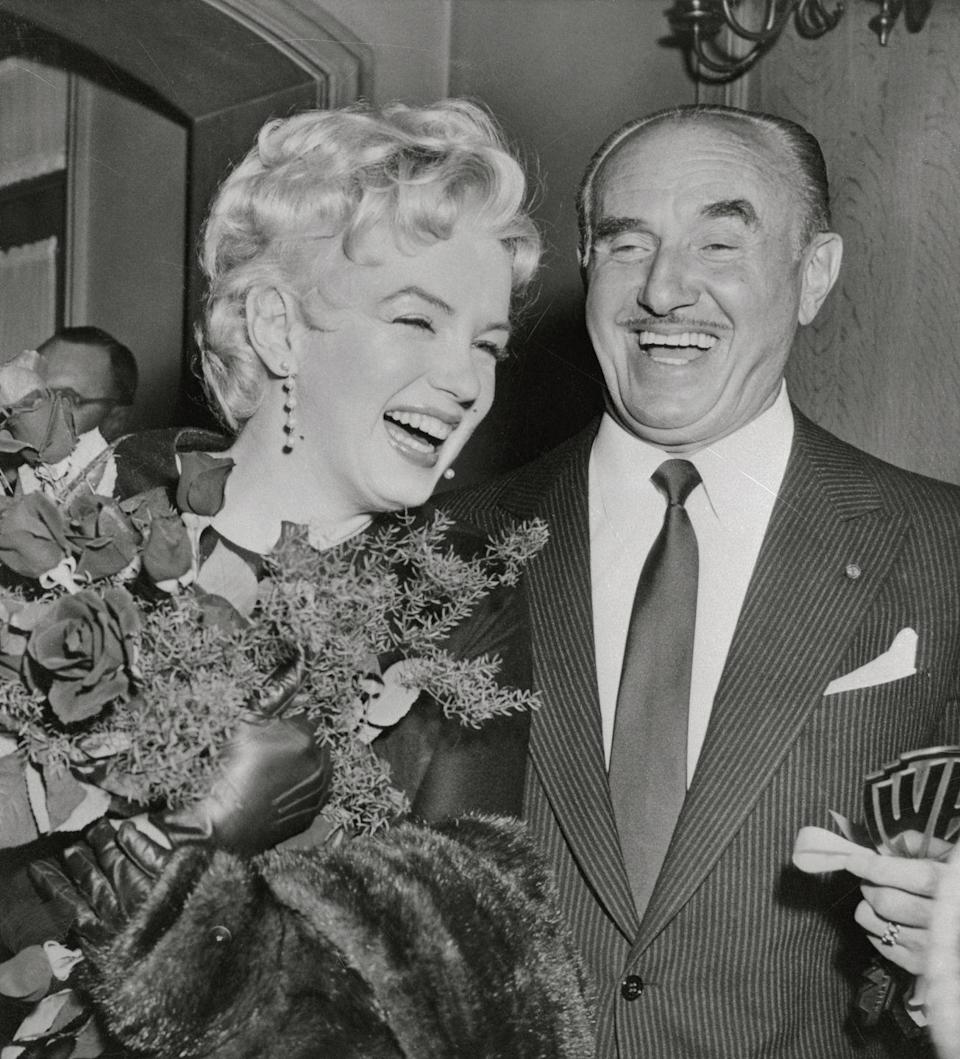 <p>Marilyn accepted flowers from Jack Warner, president of Warner Brothers, after Warner announced that Marilyn would star in a new film. </p>