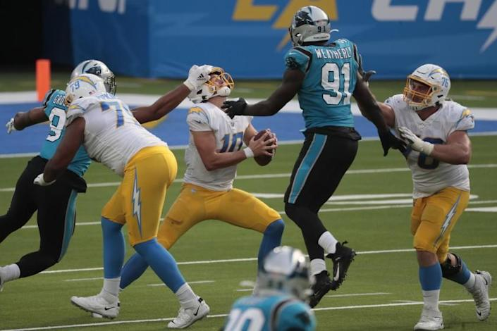 Inglewood, CA, Sunday, September 27, 2020 - Los Angeles Chargers quarterback Justin Herbert (10) is hit in the face by Carolina Panthers defensive end Yetur Gross-Matos (97) for a penalty as the Chargers drive for a late touchdown at SoFi Stadium. (Robert Gauthier/ Los Angeles Times)