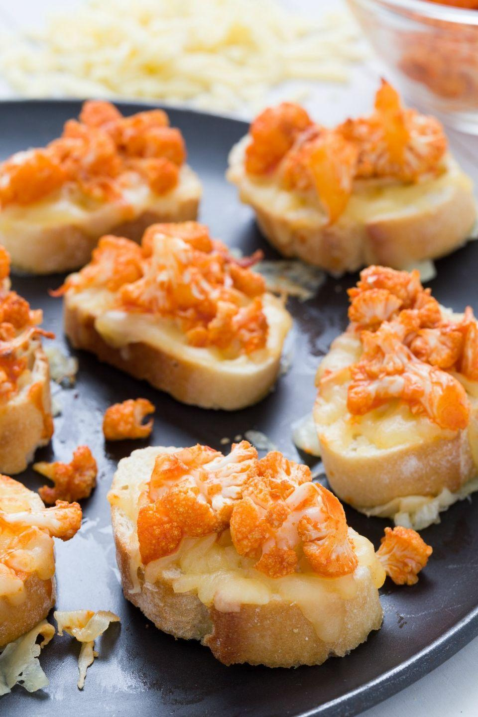 <p>If you haven't gotten on the buff cauliflower train, climb aboard: These pieces of roasted cauliflower are tossed with buffalo sauce and topped on white cheddar toasts.</p>