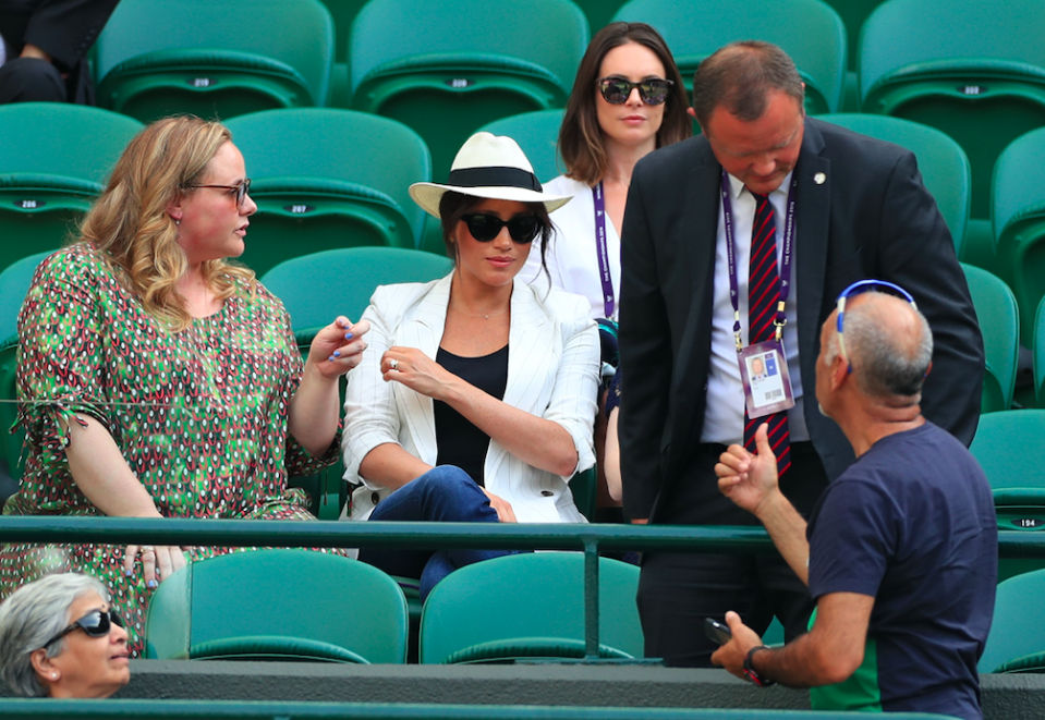 A bodyguard tells a tennis fan not to take pictures of Meghan Markle (PA)