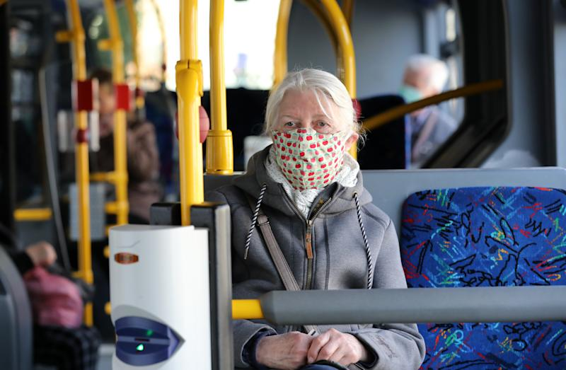 27 April 2020, Mecklenburg-Western Pomerania, Rostock: A woman is sitting in a bus with a self-made mouthguard as mouth and nose cover. From 27.04.2020 it is mandatory in Mecklenburg-Vorpommern to wear a mouth and nose cover when shopping and in public transport including taxis. Photo: Bernd Wüstneck/dpa-Zentralbild/dpa (Photo by Bernd Wüstneck/picture alliance via Getty Images)