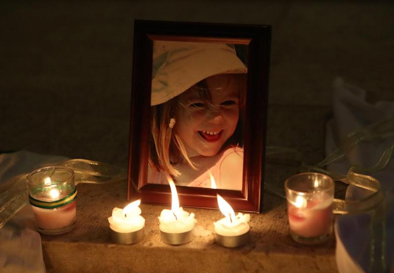 Moving image: Candles are placed next to a photo of Madeleine McCann inside the Church of Nossa Senhora da Luz in Praia Da Luz (PA)