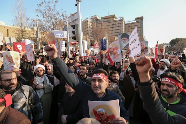 Demonstrators hold placards bearing the images of slain military commander Qasem Soleimani. (Getty)