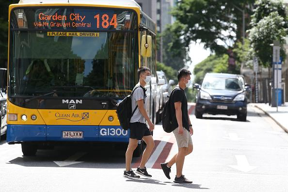 People wearing masks walk through the Brisbane CBD in front of a bus.