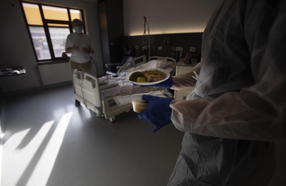A Belgian Army medic brings lunch to a patient with COVID-19 at the St. Michiel Hospital in Brussels, Tuesday, Nov. 24, 2020. The Belgian military has been called into several hospitals and care homes to alleviate the stress on healthcare personnel. (AP Photo/Virginia Mayo)