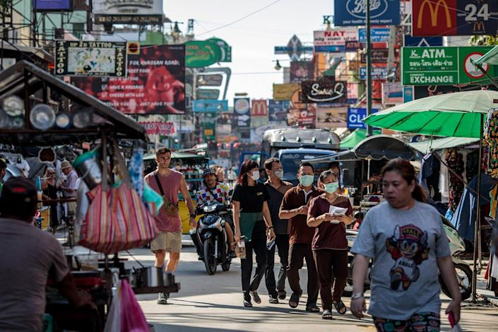 People wear facemasks While walking along Khao San Road, a popular area for tourists in Bangkok