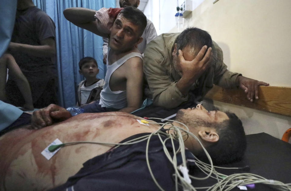 Mourners react in a hospital over the body of a man who died following an explosion in the town of Beit Lahiya, northern Gaza Strip, on Monday, May 10, 2021. The Hamas militant group launched a rare rocket strike on Jerusalem after hundreds of Palestinians were hurt in clashes with Israeli police at an iconic mosque. Israel responded Monday with airstrikes across the Gaza Strip, where 20 people, including nine children, were killed in fighting. (AP Photo/Mohammed Ali)