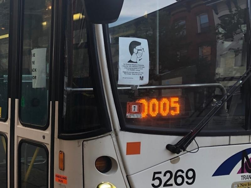 A NJ Transit bus from Hoboken to New York has a sign in front about wearing a mask, and one on the side saying people can only enter via the rear door.