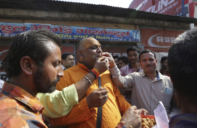 Hindus celebrate with sweets after a verdict in a decades-old land title dispute between Muslims and Hindus, in Ayodhya, India , Saturday, Nov. 9, 2019. India's Supreme Court on Saturday ruled in favor of a Hindu temple on a disputed religious ground and ordered that alternative land be given to Muslims to build a mosque. The dispute over land ownership has been one of the country's most contentious issues. (AP Photo/Rajesh Kumar Singh)