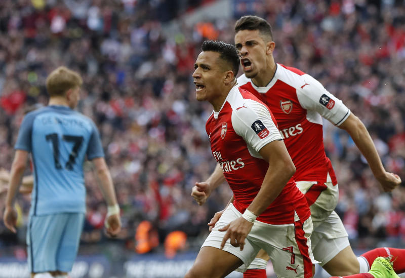 Arsenal's Alexis Sanchez, center, celebrates after scoring his side's second goal during the English FA Cup semifinal soccer match between Arsenal and Manchester City at Wembley stadium in London, Sunday, April 23, 2017. (AP Photo/Kirsty Wigglesworth)