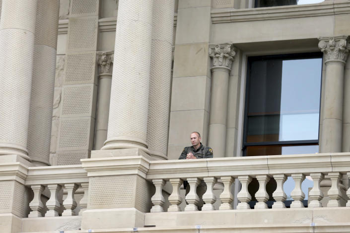 In this Wednesday, Jan. 6, 2021, photo, a Wyoming Highway Patrol officer watches a peaceful protest from the upper levels of the Capitol in downtown Cheyenne, Wyo. The protest was in response to the murder of George Floyd, as well as Breonna Taylor and many other people of color across the country, and was meant to show unity for change. Wyoming Gov. Mark Gordon quietly mobilized dozens of National Guard troops in case of any violence at the state Capitol in Cheyenne, Wyo., in January. The deployment came to light Friday, March 5, 2021, after an Associated Press inquiry after the Jan. 6 riot at the U.S. Capitol, which left five dead. (Michael Cummo/The Wyoming Tribune Eagle via AP)