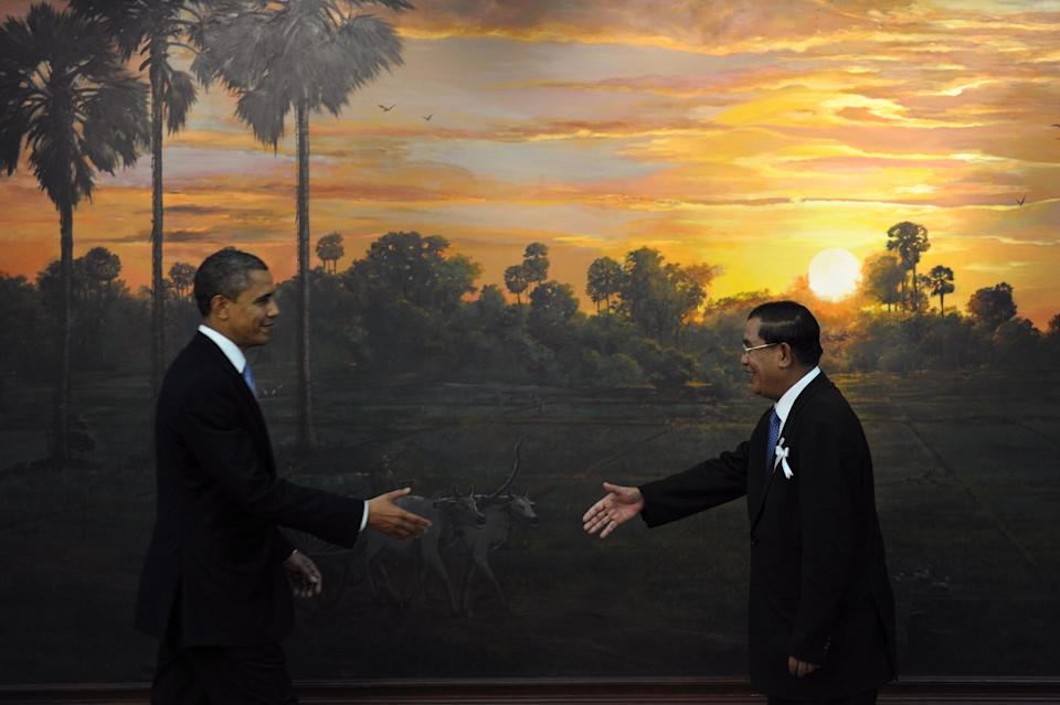 U.S. President Barack Obama (L) and Cambodian Prime Minister Hun Sen (R) reach out to shake hands on arrival at the Peace Palace for the Association of Southeast Asian Nations (ASEAN) and US summit in Phnom Penh on Nov. 19, 2012 following the 21st ASEAN Leaders Summit.