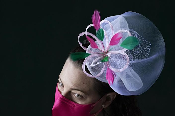 A woman wears a small tulle hat with a pink flower shaped ribbon and green and dark pink feathers, plus a dark pink mask.
