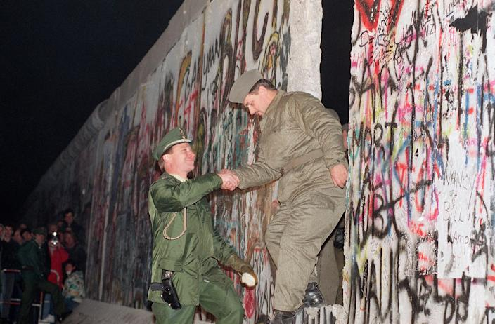 A West German policeman, left, gives a helping hand to an East German border guard who climbs through a gap of the Berlin Wall when East Germany opened another passage at Potsdamer Platz in Berlin, Nov. 12, 1989.