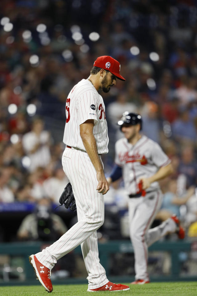 Philadelphia Phillies starting pitcher Zach Eflin, left, walks back to the mound as Atlanta Braves' Matt Joyce, right, rounds on the way home after a three-run home run by Tyler Flowers during the fourth inning of a baseball game Wednesday, Sept. 11, 2019, in Philadelphia. (AP Photo/Matt Slocum)