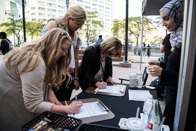 """Rowaida Abdelaziz (right) signs up Kelly Smith, Rachel Kristensen and Kristine Rouleau on Oct. 3 as part of """"Listen To America: A HuffPost Road Trip."""" The news outlet will visit more than 20 cities on its tour across the country."""