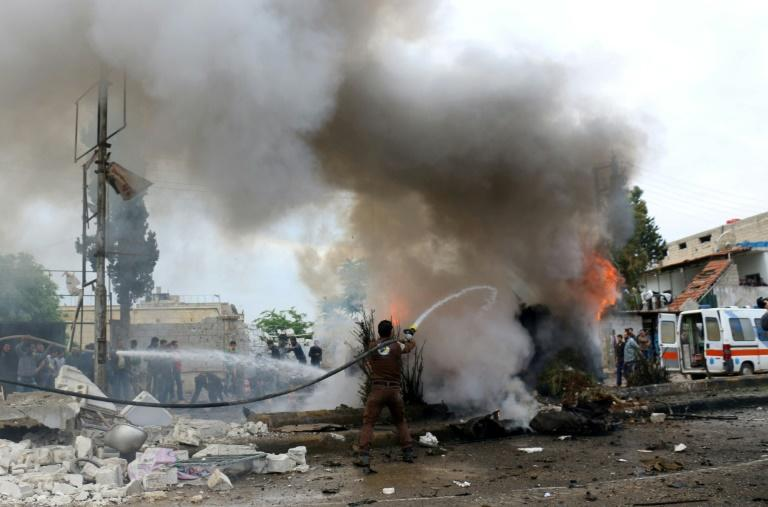 A member of the Syrian civil defence tries to extinguish fire from a burning vehicle following a reported car bomb explosion in the rebel-held town of Azaz in northern Syria on May 3, 2017