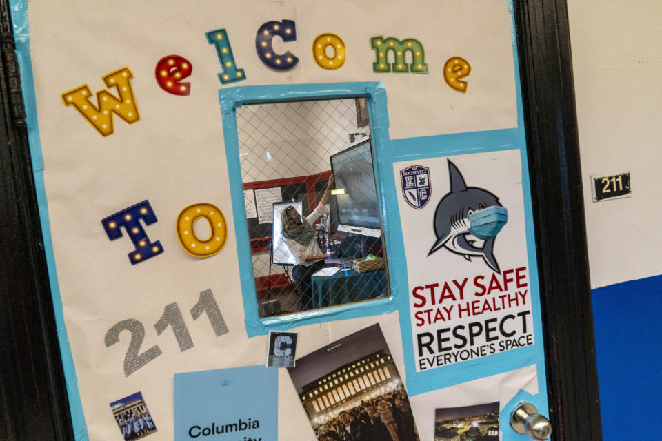 Framed through a classroom window, a teacher conducts a class during the coronavirus outbreak at Roosevelt High School - Early College Studies, Thursday, Oct. 15, 2020, in Yonkers, N.Y. (AP Photo/Mary Altaffer)