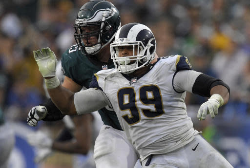 FILE - In this Dec. 10, 2017, file photo, Los Angeles Rams defensive end Aaron Donald, right, gets past Philadelphia Eagles offensive tackle Lane Johnson during an NFL football game in Los Angeles. Donald is not attending the Rams' mandatory minicamp while he continues his lengthy quest for a lucrative new contract. Donald wasn't on the field with his teammates for the Rams' first minicamp workout Tuesday, June 12, 2018. and he wasn't at their training complex for their off-field commitments Monday, either. The NFL Defensive Player of the Year also skipped the Rams' voluntary workout program over the previous two months. (AP Photo/Mark J. Terrill, File)