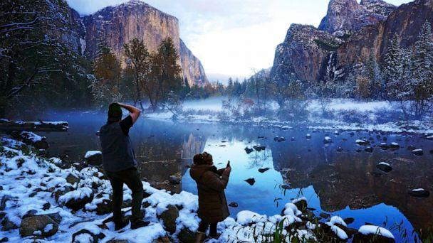 PHOTO: Erick Jensen, left, of Seattle, and Ruth Reyes, right, of Los Angeles, prepare to photograph the sunset in Yosemite Valley, Nov. 9, 2020, following a snowstorm in Yosemite National Park, Calif. (Eric Paul Zamora/The Fresno Bee via AP)