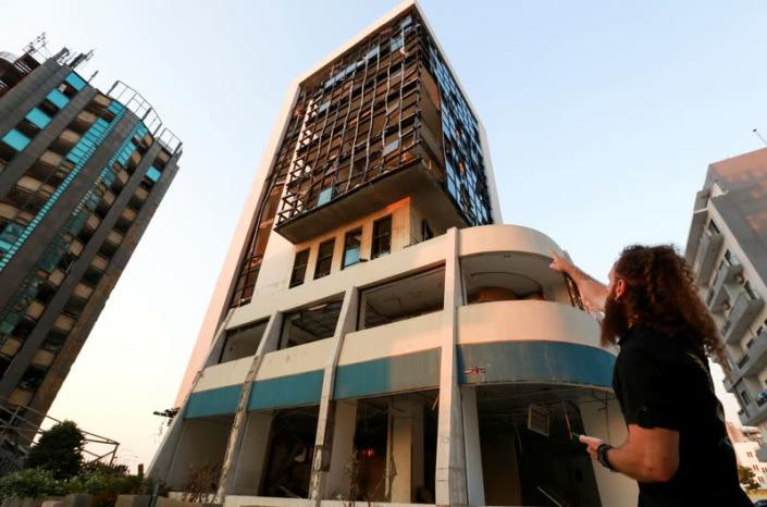 Shady Rizk, a survivor wounded during last year's Beirut port blast, points at the damaged office where he was working at the moment of the blast, in Beirut