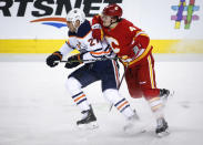 Edmonton Oilers' Milan Lucic, left, is checked by Calgary Flames' Rasmus Andersson, of Sweden, during the first period of an NHL hockey game Saturday, Nov. 17, 2018, in Calgary, Alberta. (Jeff Macintosh/The Canadian Press via AP)