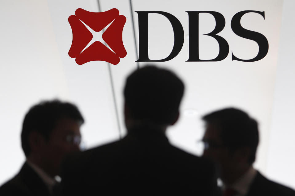 People talk next to a DBS logo at a DBS function in Singapore July 5, 2013. REUTERS/Edgar Su (SINGAPORE - Tags: BUSINESS LOGO)
