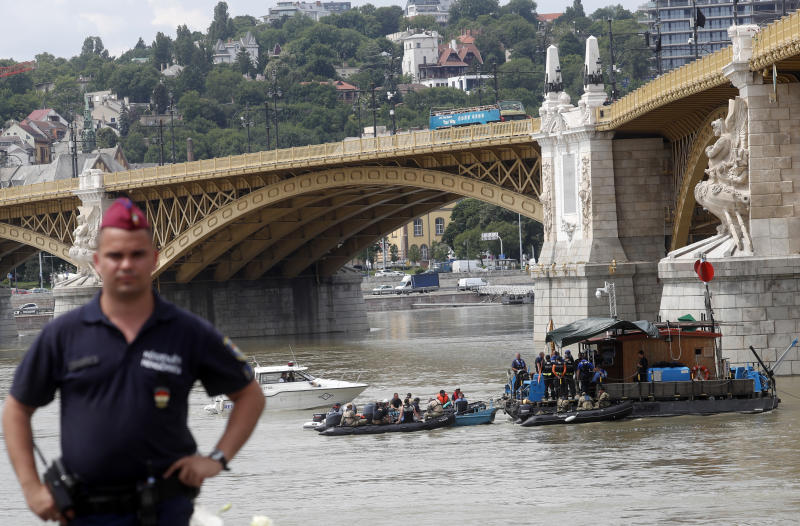 FILE - In this Tuesday, June 4, 2019 file photo, a Hungarian police officer stands on the banks of the Danube River where a sightseeing boat capsized in Budapest, Hungary. Hungarian police say a South Korean woman recovered from the Danube River has been identified as the 27th fatality of the May 29 crash between a tour boat and a cruise ship. Police said Saturday, July 6 that the body was found some 58 kilometers (36 miles) downstream from the scene of the accident at Budapest's Margit Bridge.(AP Photo/Laszlo Balogh, file)