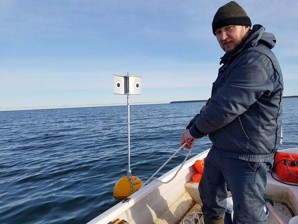 Field worker Rein Nellis on his boat deploying one of the deterrent within the observation plot (Andres Kalamees/PA)