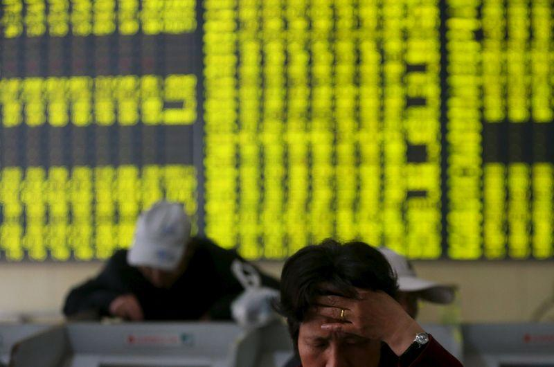 Investors check stock information at a brokerage house in Nantong