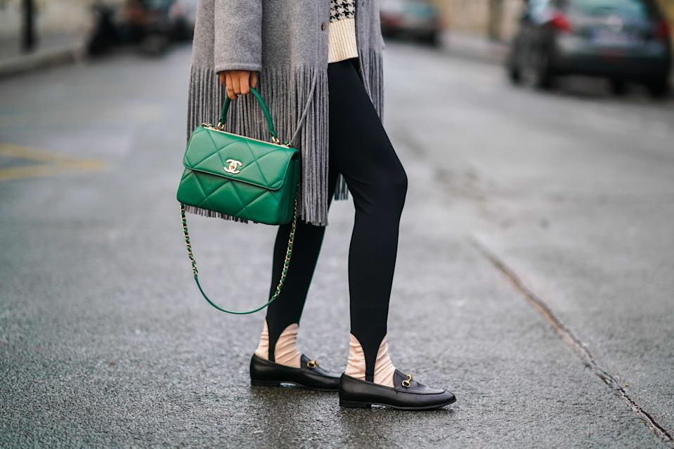 PARIS, FRANCE - DECEMBER 14: Gabriella Berdugo wears a gray wool coat with fringes from Dorothee Schumacher, black leggings with strappy legs, black leather Gucci loafers shoes, a green quilted leather Chanel bag, on December 14, 2020 in Paris, France. (Photo by Edward Berthelot/Getty Images)