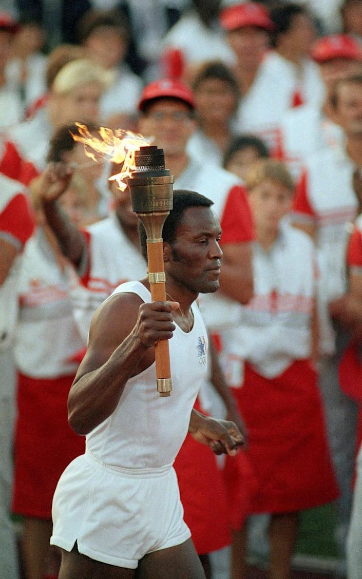 Rafer Johnson carrying the Olympic torch through the Los Angeles Memorial Coliseum before lighting the Olympic flame and formally launching the 1984 Games - Peter Leabo/ AP