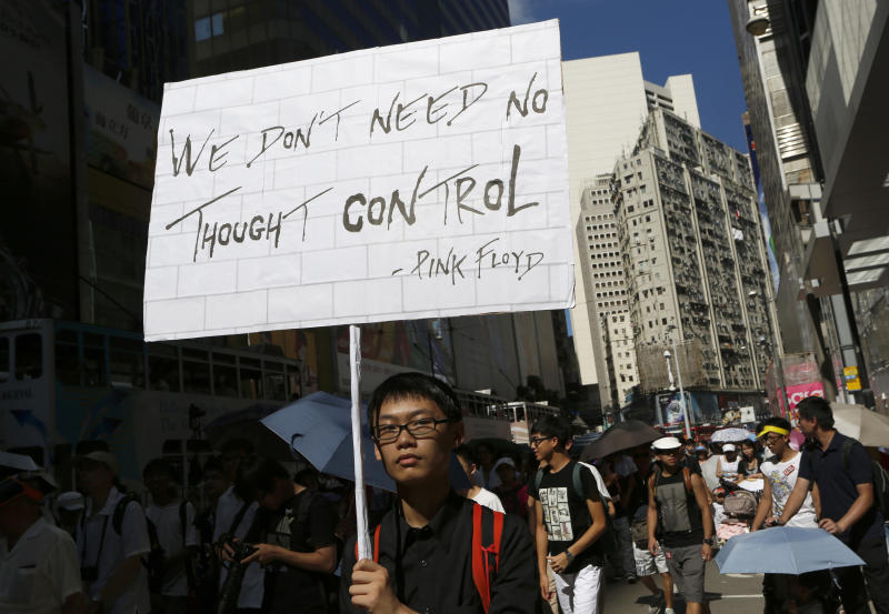 A protester holds a placard during a march in a downtown street in Hong Kong Sunday, July 29, 2012 to protest the upcoming introduction in schools of Chinese patriotism classes that they fear will lead to brainwashing. Teachers, parents, students and pro-democracy activists marched Sunday to the government headquarters of the semiautonomous territory to protest against the new curriculum, which authorities are encouraging schools to begin using when classes resume in September. (AP Photo/Vincent Yu)