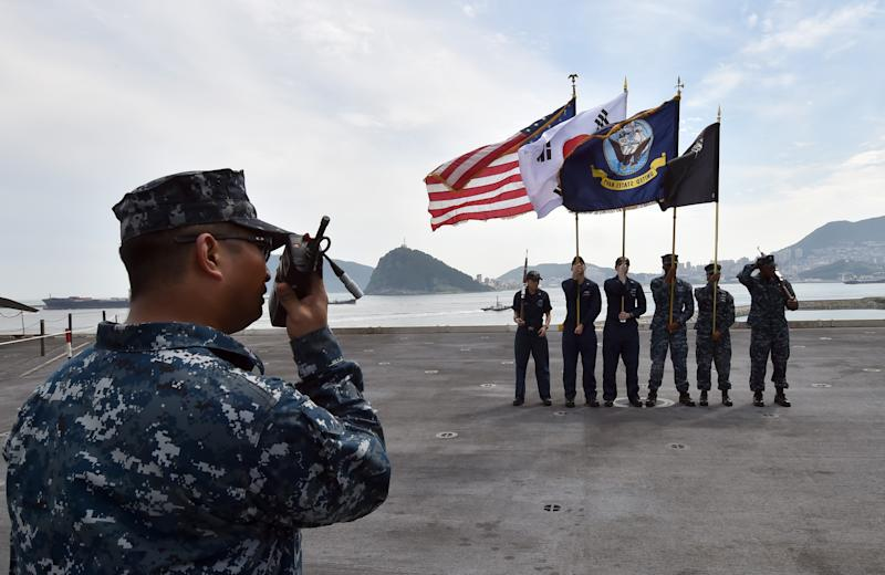 Crew members hold US (L) and South Korean (2nd L) national flags on the flight deck of US nuclear powered aircraft carrier USS George Washington, at a S.Korean naval port in Busan, on July 11, 2014 (AFP Photo/Jung Yeon-Je)