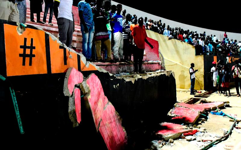 People stand before a collapsed wall at Demba Diop stadium  - Credit: Seyllou/AFP