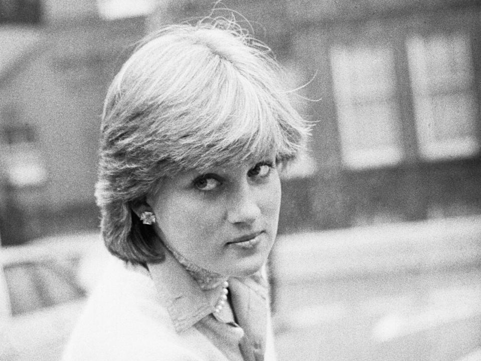 Lady Diana Spencer opens a car door as she holds her coat, London, UK, 13th November 1980. (Getty Images)
