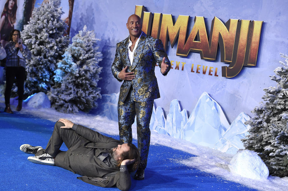 "Cast members Jack Black, laying down, and Dwayne Johnson pose for photographers at the Los Angeles premiere of ""Jumanji: The Next Level"" at the TCL Chinese Theatre on Monday, Dec. 9, 2019 in Calif. (Photo by Jordan Strauss/Invision/AP)"