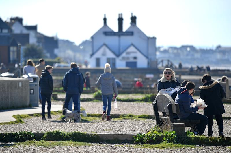 People enjoy the Spring sunshine on the seafront at Whitstable, east of London on Mother's Day, March 22, 2020. - Up to 1.5 million vulnerable people in Britain, identified as being most at risk from the coronavirus epidemic, should stay at home for at least 12 weeks, the government said Sunday. (Photo by Ben STANSALL / AFP) (Photo by BEN STANSALL/AFP via Getty Images)