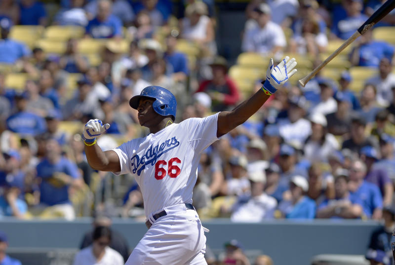 Los Angeles Dodgers' Yasiel Puig, right, hits a three-run home run during the sixth inning of a baseball game against the Arizona Diamondbacks, Sunday, April 20, 2014, in Los Angeles. (AP Photo/Mark J. Terrill)