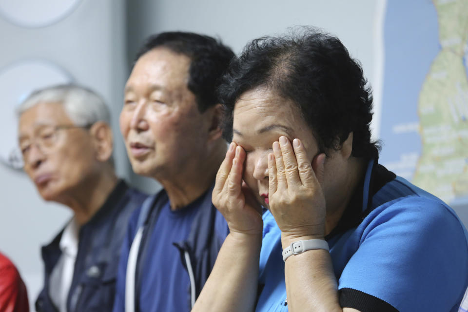 Shin Yun-sun, right, wipes her tears during an interview at her house in Seoul, South Korea, Wednesday, July 29, 2020. Shin, 75, has spent decades pestering government officials, digging into records and searching burial grounds on Russia's desolate Sakhalin island, desperately searching for traces of a father she never met. The thousands of husbands and fathers who never returned from Sakhalin after eight decades is a largely forgotten legacy of Japan's brutal rule of the Korean Peninsula before the end of World War II. (AP Photo/Ahn Young-joon)