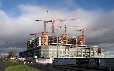 <span>Cranes stand idle above the Midland Metropolitan Hospital construction site</span> <span>Credit: James Beck/Bloomberg </span>